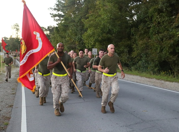 Col. Matthew G. St. Clair, commanding officer, Ground Combat Element Integrated Task Force, leads the task force in a three-mile run aboard Marine Corps Base Camp Lejeune, North Carolina, Oct. 17, 2014. Throughout the run, Marines shouted cadence and waved guid-ons high. From October 2014 to July 2015, the Ground Combat Element Integrated Task Force will conduct individual and collective skills training in designated combat arms occupational specialties in order to facilitate the standards based assessment of the physical performance of Marines in a simulated operating environment performing specific ground combat arms tasks. (U.S. Marine Corps photo by Cpl. Paul S. Martinez/Released)