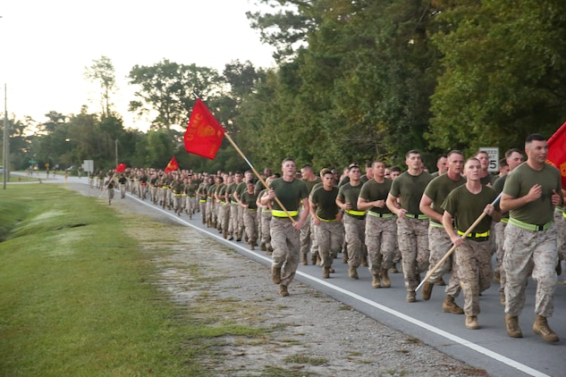 Marines with the Ground Combat Element Integrated Task Force conduct a three-mile run aboard Marine Corps Base Camp Lejeune, North Carolina, Oct. 17, 2014. Throughout the run, Marines shouted cadence and waved guid-ons high. From October 2014 to July 2015, the Ground Combat Element Integrated Task Force will conduct individual and collective skills training in designated combat arms occupational specialties in order to facilitate the standards based assessment of the physical performance of Marines in a simulated operating environment performing specific ground combat arms tasks. (U.S. Marine Corps photo by Cpl. Paul S. Martinez/Released)