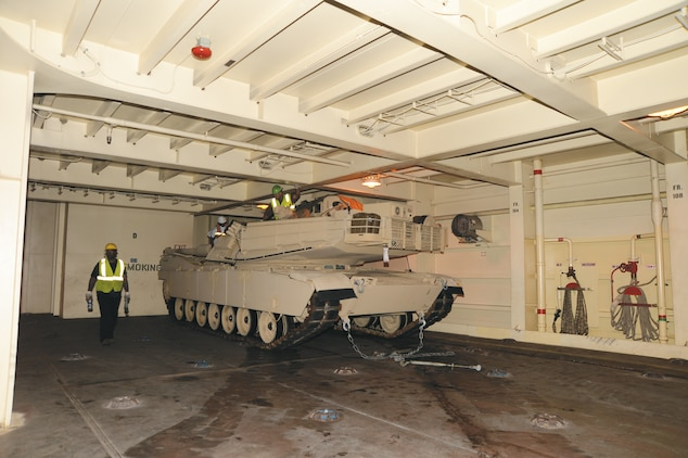 Blount Island Command, Jacksonville, Fla., employees prepare a tank to be secured on the USNS Pfc. Dewayne T. Williams, recently.