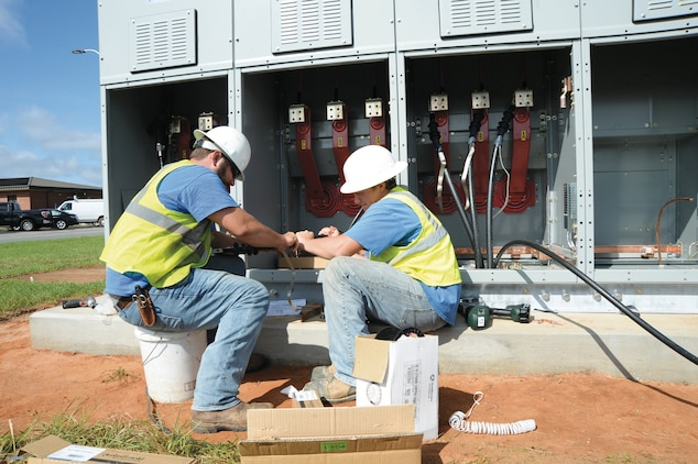 Electricians from A West Enterprises, Albany, Ga., complete wiring for a generator, which will supply power to buildings 3500 and 3600 in the event of a power outage.