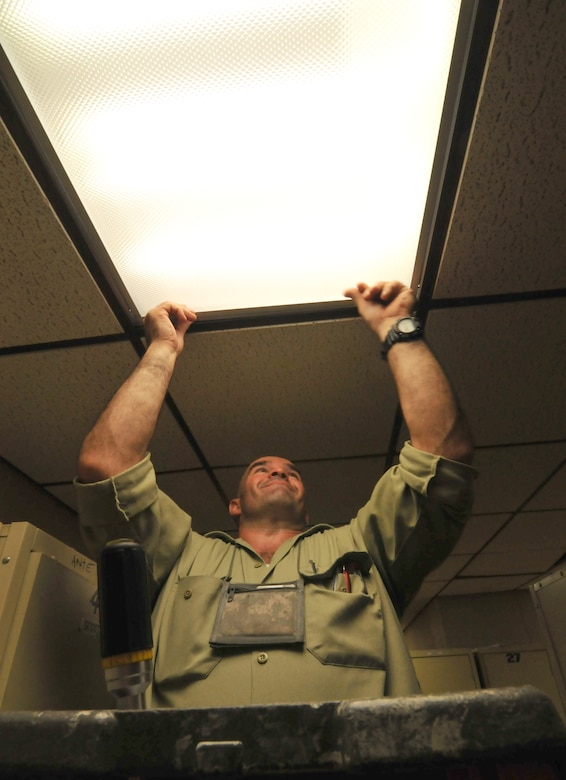 Peter Cote, electrician with the 177th Fighter Wing of the New Jersey Air National Guard, completes the installation of higher efficiency T8 fluorescent bulbs and electronic ballasts at the base on Oct. 10, 2014. October is the Department of Defense's Energy Awareness Month. (U.S. Air National Guard photo by Master Sgt. Andrew J. Moseley/Released)