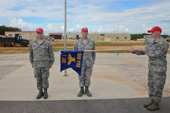 Master Sgt. Michael English, 554th RED HORSE Squadron NCO in charge of emergency management, unfurls the flag Oct. 15, 2014, during the opening ceremony of Silver Flag on Northwest Field at Andersen Air force Base, Guam.  Silver Flag training is designed to setup operations at bare-base locations and features bed down planning, base recovery, command and control and airfield recovery. (U.S. Air Force photo by Staff Sgt. Robert Hicks/Released)