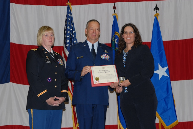 Nevada Army National Guard Lt. Col. Mary Devine (left), and Nevada Air National Guard Brig. Gen. David Snyder (center) present Sharon Landsberry with the National Guard Association's Valley Forge Cross for Heroism during a ceremony on Sunday at the Reno-Sparks Convention Center.  Sharon's late husband, Master Sgt. Michael Landsberry, gave his life to save his students during a shooting incident on 21 Oct. 2013, at Sparks Middle School.  U.S. Air Force photo by Senior Airman Ashif Halim. (RELEASED).