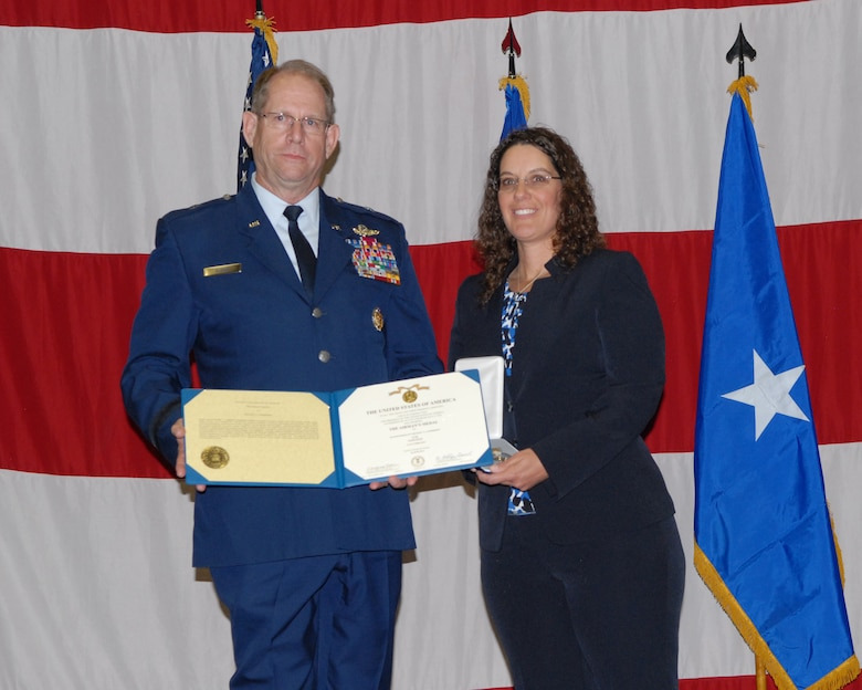 Nevada Adjutant General, Brig. Gen. William Burks (left), presents the  Airman's Medal  to Sharon Landsberry during a ceremony on Sunday at the  Reno-Sparks Convention Center.  Sharon's husband, Master Sgt. Michael  Landsberry, gave his life to save his students during a shooting incident on  21 Oct. 2013, at Sparks Middle School.  USAF photo by Senior Airman Ashif Halim.  (RELEASED)