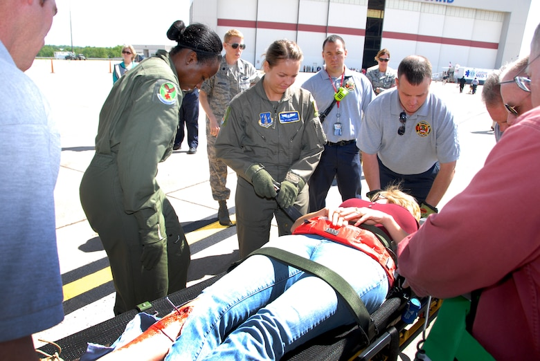 U.S. Air Force Airmen from the 156th Aeromedical Evacuation Squadron, North Carolina Air National Guard, secure a non-ambulatory community volunteer victim to a gurney in conjunction with firemen from the Charlotte-Mecklenburg Fire Department, participating in the Western N.C. National Disaster Medical System (NDMS) Shake, Rattle, & Roll Exercise 2013 at the NCANG base, Charlotte-Douglas Intl. Airport, May 8, 2013. (U.S. Air National Guard photo by Master Sgt. Rich Kerner, 145th Public Affairs/Released)