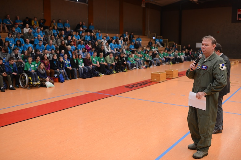 U.S. Air Force Col. Lars Hubert, 52nd Fighter Wing vice commander, addresses volunteers from the Spangdahlem community along with St. Martin School students and teachers in the Skelton Memorial Fitness Center on Spangdahlem Air Base, Germany, Oct. 16, 2014. The St. Martin School takes care of children with special needs, and the Spangdahlem community plans this event every year to allow the children to interact, play, and socialize in a safe and open environment. (U.S. Air Force photo by Senior Airman Gustavo Castillo/Released)