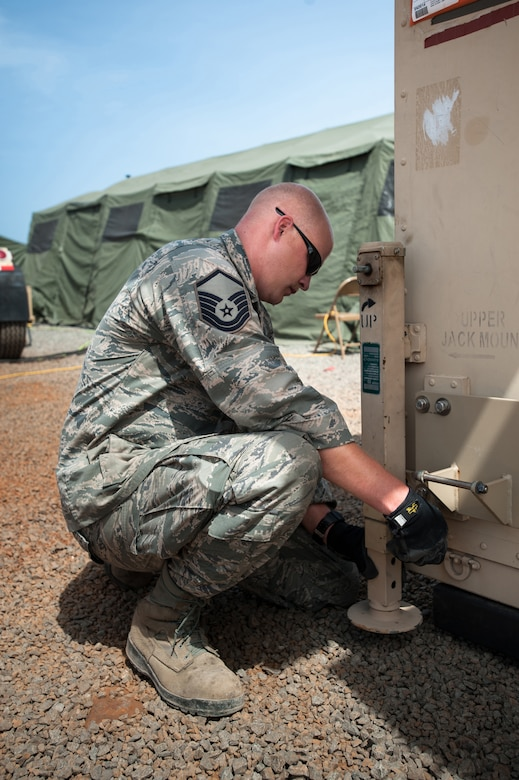 U.S. Air Force Master Sgt. Matthew Hourigan of the Kentucky Air National Guard's 123rd Contingency Response Group installs leveling jacks on a mobile airfield operations center at Léopold Sédar Senghor International Airport in Dakar, Senegal, Oct. 17, 2014, in support of Operation United Assistance, the U.S. Agency for International Development-led, whole-of-government effort to respond to the Ebola outbreak in West Africa. The Airmen are operating an Intermediate Staging Base in Dakar to funnel humanitarian aid and military support equipment into affected areas, working in concert with Soldiers from the U.S. Army's 689th Rapid Port Opening Element to staff a Joint Task Force-Port Opening. (U.S. Air National Guard photo by Maj. Dale Greer)