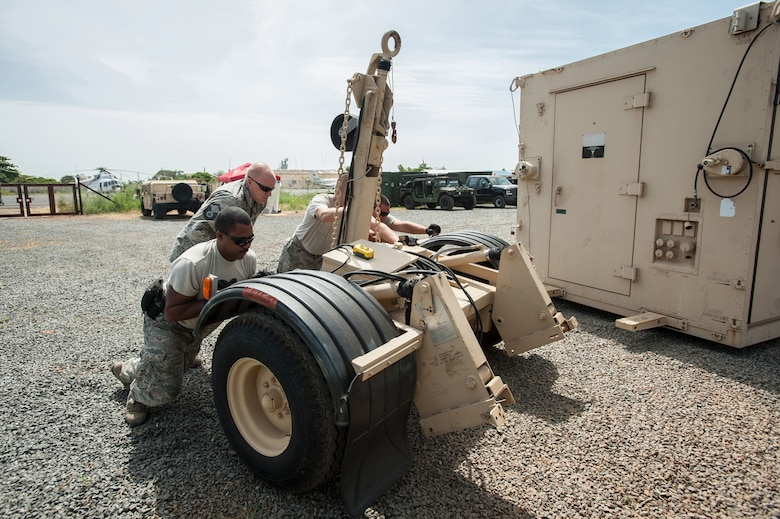 Airmen from the Kentucky Air National Guard's 123rd Contingency Response Group remove the transport wheels from a mobile airfield operations center at Léopold Sédar Senghor International Airport in Dakar, Senegal, Oct. 17, 2014, in support of Operation United Assistance, the U.S. Agency for International Development-led, whole-of-government effort to respond to the Ebola outbreak in West Africa. The Airmen are operating an Intermediate Staging Base in Dakar to funnel humanitarian aid and military support equipment into affected areas, working in concert with Soldiers from the U.S. Army's 689th Rapid Port Opening Element to staff a Joint Task Force-Port Opening. (U.S. Air National Guard photo by Maj. Dale Greer)