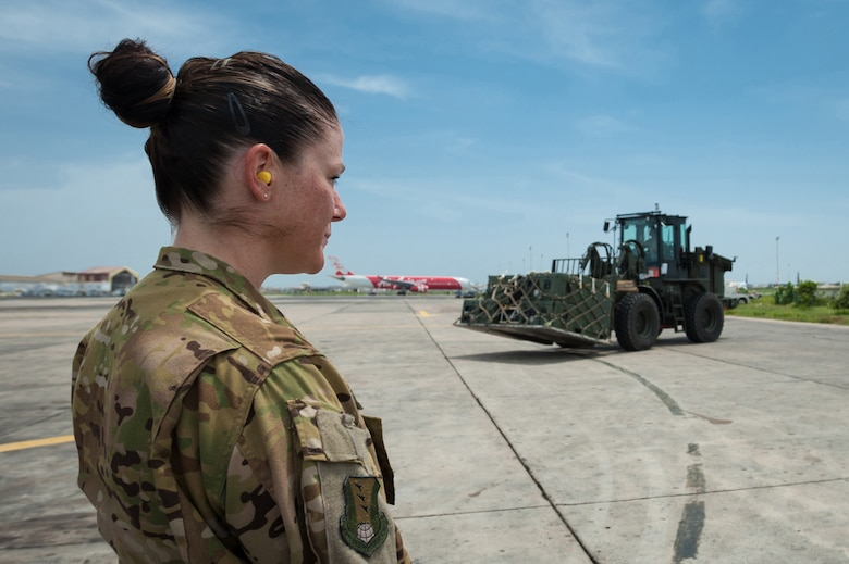 U.S. Air Force Tech. Sgt. Meghan Donahue, a member of a fly-away security detail from the 435th Air Expeditionary Wing at Ramstein Air Base, Germany, provides overwatch of a Ramstein C-130 Hercules aircraft as U.S. Air Force Senior Airman Alex Vincent, an aerial porter from the Kentucky Air National Guard's 123rd Contingency Response Group, prepares to load a pallet of red blood cells and frozen plasma on the aircraft Oct. 10, 2014, at Léopold Sédar Senghor International Airport in Dakar, Senegal. The Airmen are supporting Operation United Assistance, the U.S. Agency for International Development-led, whole-of-government effort to respond to the Ebola outbreak in West Africa. (U.S. Air National Guard photo by Maj. Dale Greer)