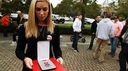 Erin Vasselian holds a Bronze Star Medal following a ceremony where her husband, Sgt. Daniel Vasselian, was posthumously awarded the Bronze Star Medal with Combat Distinguishing Device, Oct. 13, in front of the American Legion's Lewis V. Dorsey Post 112 War Memorial in Abington, Mass. Daniel was posthumously awarded the Bronze Star Medal with Combat Distinguishing Device for combat actions while on his third deployment to Afghanistan. Erin Vasselian, and parents, Karen and Mark Vasselian, each were presented with medals during the ceremony. Daniel was killed in action Dec. 23, 2013 in Helmand Province, Afghanistan. (Photo by Sgt. Richard Blumenstein)