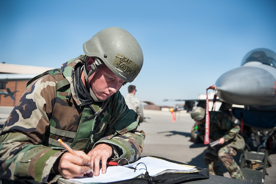 Senior Airman Justin Torrey, 8th Aircraft Maintenance Squadron 80th Aircraft Maintenance Unit, Kunsan Air Base, Republic of Korea, fills out aircraft forms during a quarterly load crew competition at Osan Air Base, ROK, Oct. 17, 2014. Load crew members are evaluated on their safety, speed, and use of the checklist. (U.S. Air Force photo by Senior Airman Matthew Lancaster)