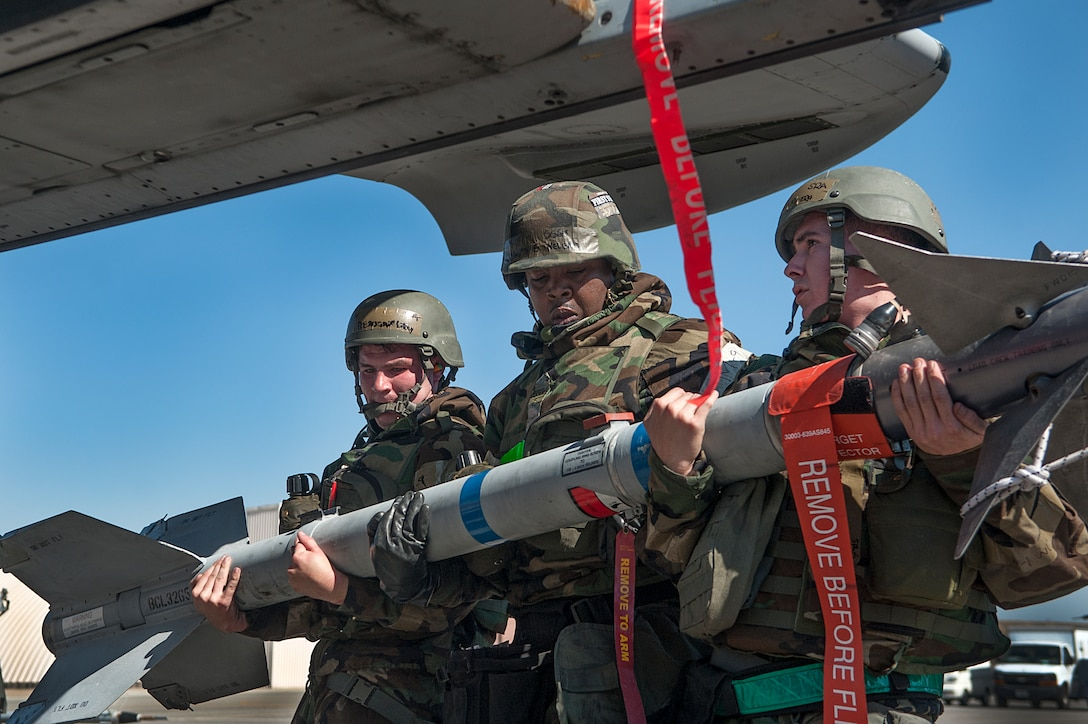 Senior Airman Benjamin Lilley, Staff Sgt. Kenneth Nelems, and Senior Airman Hunter Rivera, all 51st Aircraft Maintenance Squadron 25th AMU weapons load crew members, load an Air Intercept Missile-9M Sidewinder air-to-air missile onto an A-10 Thunderbolt II during a quarterly load crew competition at Osan Air Base, Republic of Korea, Oct. 17, 2014. Load crew competitions promote a safe competitive environment where Airmen display their skills and ability to apply their training. (U.S. Air Force photo by Senior Airman Matthew Lancaster)