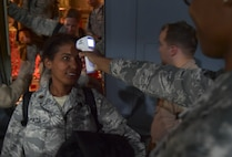 Maj. Mayra Zapata gets her temperature taken by Tech. Sgt. Saquadrea Crosby as she deplanes a C-130J Super Hercules Oct. 19, 2014, at Ramstein Air Base, Germany. Any personnel traveling into Ramstein AB from Ebola-affected areas will be medically screened upon their arrival and cleared by public health for onward travel to ensure the health and safety of all passengers, aircrew and members of the Kaiserslautern Military Community. Zapata is assigned to the 633rd Medical Operations Squadron and Crosby is a 86th Aerospace Medicine Squadron public health NCO in charge. (U.S. Air Force photo/Staff Sgt. Sara Keller)