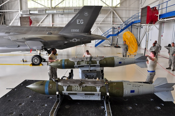 Airmen with the 58th Aircraft Maintenance Unit crew one prepare to load a GBU-31 joint direct attack munition on to an F-35A Lightning II during a qualification load Oct. 10, 2014, at Eglin Air Force Base, Fla. The F-35A is now one step closer to its initial operational capability with the first weapons load crew qualification. The newly qualified crewmembers will continue to hone their skills and become experts at their jobs so they can train the weapons load crews at other bases receiving the F-35A. (U.S. Air Force photo/Staff Sgt. Marleah Robertson)