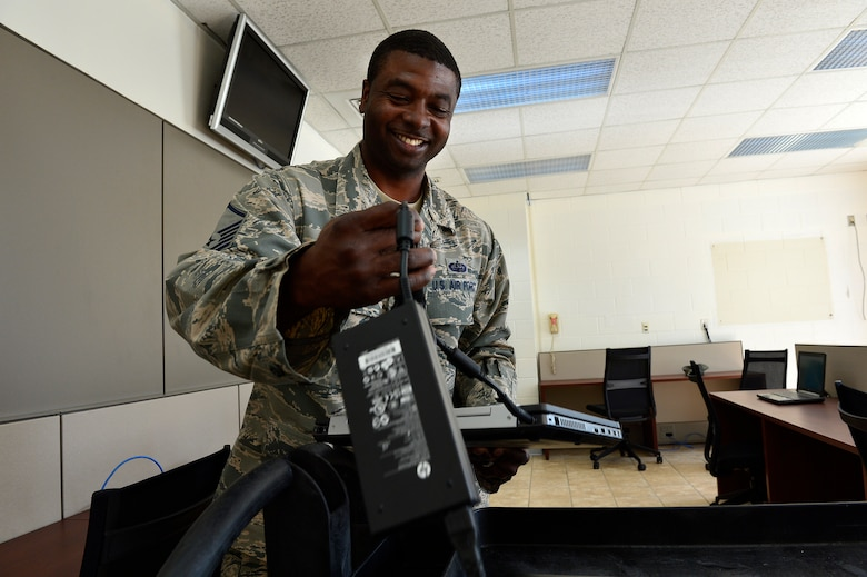 MCGHEE TYSON AIR NATIONAL GUARD BASE, Tenn. -- Master Sgt. Raymond Harris, Cyber Operations technician for the I.G. Brown Training and Education Center, installs laptop computers Oct. 22, 2014, here in the Morrisey Hall classroom building. The 21 computers as well as recently installed furniture are part of two  cyber cafes coming online near the downstairs entrances. (U.S. Air National Guard photo by Master Sgt. Mike R. Smith/Released)