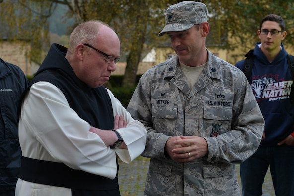 U.S. Air Force Lt. Col. Christopher Meeker, 52nd Civil Engineer Squadron commander and native of Manito, Ill.,  talks with Father Ignatius Fritsch in the cloister of Himmerod Abbeyin Grosslittgen, Germany,Oct. 21, 2014. Airmen from the 52nd CES volunteered to help pick apples for the monks and received a free lunch for helping out. (U.S. Air Force photo by Airman 1st Class Kyle Gese/Released)
