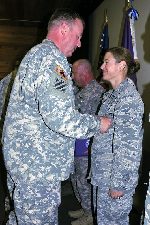 U.S. Army Col. Kirk C. Dorr, Joint Task Force-Bravo commander, pins the Military Outstanding Volunteer Service Medal on U.S. Air Force Capt. Sherri Pierce, JTF-Bravo Logistics director, during a commander's call last month while deployed to Soto Cano Air Base, Honduras. Pierce received the award for completing 11 volunteer events equaling more than 40 hours of service while deployed. (Courtesy photo)
