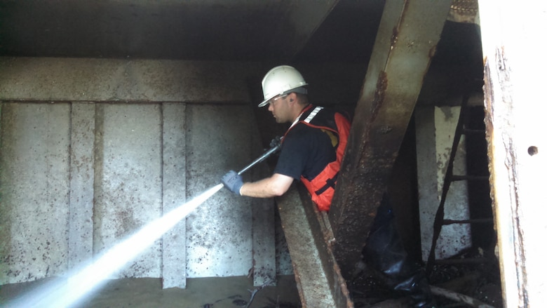 Nathan Payne, summer laborer, uses a hose to wash mud and debris out of one of the tainter gates at Newburgh Locks and Dam, Newburgh, Ind.