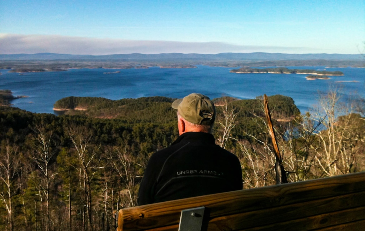 "Alpha Dog Jerry Shields enjoys the view from the ""Traildog Vista"" bench on the Lake Ouachita Vista Trail at Bear Mountain.