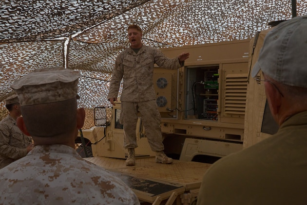 Cpl. Elijah Schellhardt, a Marine Corps Tactical Systems Support Activity Common Aviation Command Control System (CAC2S) support team member, and native of Frederick, Md., shows visiting VIPs the shellback Humvee used to house the CAC2S Phase II servers at the Stoval Auxiliary Airfield, on Marine Corps Air Station Yuma, Ariz., Oct. 8. The shellback Humvee concept provides superior system mobility over the traditional use of large trucks for transport of the aging Marine Air Command and Control System CAC2S is slated to replace.