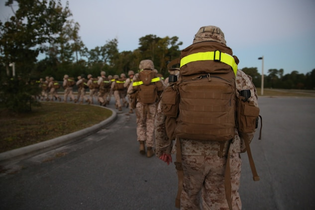 Marines with Headquarters and Service Company, Ground Combat Element Integrated Task Force, conduct a combat conditioning hike aboard Marine Corps Base Camp Lejeune, North Carolina, Oct. 23, 2014. The company hiked approximately four miles. From October 2014 to July 2015, the Ground Combat Element Integrated Task Force will conduct individual and collective skills training in designated combat arms occupational specialties in order to facilitate the standards based assessment of the physical performance of Marines in a simulated operating environment performing specific ground combat arms tasks. (U.S. Marine Corps photo by Cpl. Paul S. Martinez/Released)