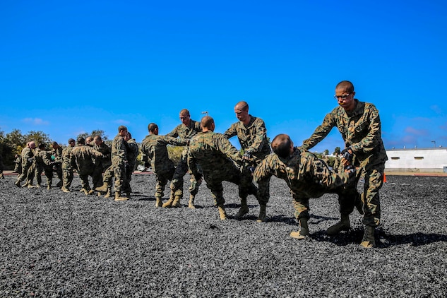 Recruits with Echo Company, 2nd Recruit Training Battalion, perform the leg sweep technique during their Marine Corps Martial Arts Program test at Marine Corps Recruit Depot, Oct. 8. The recruits were assigned a martial arts instructor who ensured they were executing each technique correctly.