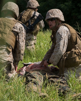 Petty Officer 2nd Class Joshua Rogers, right, from Martin, Georgia, responds to a simulated wounded enemy during a medical evacuation drill Sept. 30 at the Kin Blue Training Area. Rogers was part of the quick reaction force that gained control over two mock enemy positions. Marines and sailors are taught to provide first aid to enemy personnel as well as their own forces. Rogers is with 3rd Medical Battalion, 3rd Marine Logistics Group, III Marine Expeditionary Force. (U.S. Marine Corps photo by Lance Cpl. Rebecca Elmy/Released)