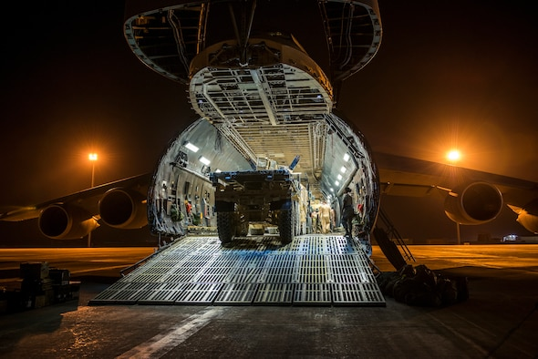 Airmen from the 9th Airlift Squadron and 455th Expeditionary Aerial Port Squadron with Marines from the Marine Expeditionary Brigade load vehicles into a C-5M Super Galaxy Oct. 6, 2014, at Camp Bastion, Afghanistan. Airmen and Marines loaded more than 266,000 pounds of cargo onto the C-5M as part of retrograde operations in Afghanistan. During this mission, the crew reached more than 11 million pounds of cargo transported in a 50-day period. (U.S. Air Force photo by Staff Sgt. Jeremy Bowcock)