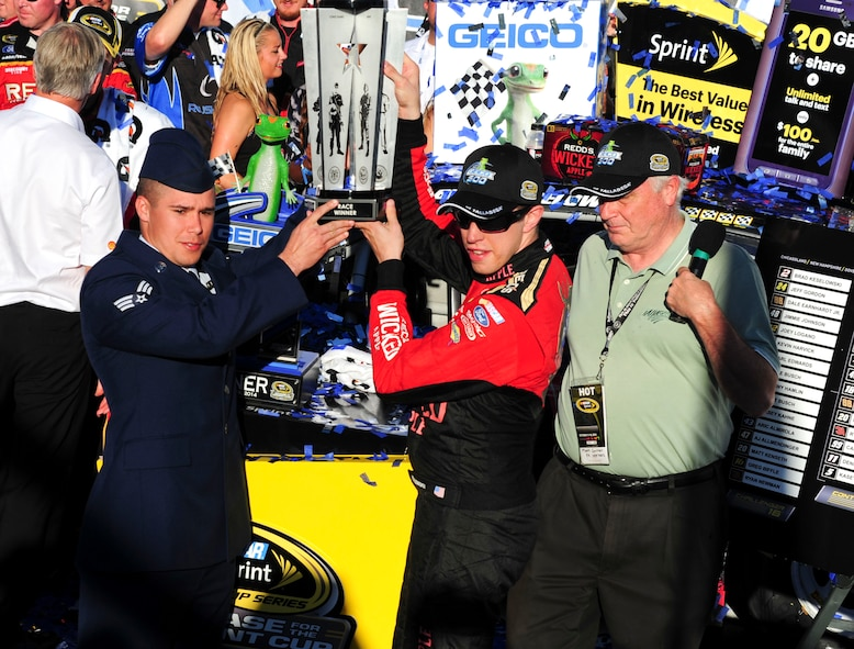 Senior Airman Donald Googe Jr., 42nd Air Base Wing Legal Office paralegal, presents the Freedom Trophy to the Geico 500 winner, Brad Keselowski, at the Talladega Superspeedway in Talladega, Ala., Oct. 19, 2014. The Freedom Trophy showcases the five branches of the military to honor and recognize  military members. (U.S. Air Force photo by Airman 1st Class Alexa Culbert)