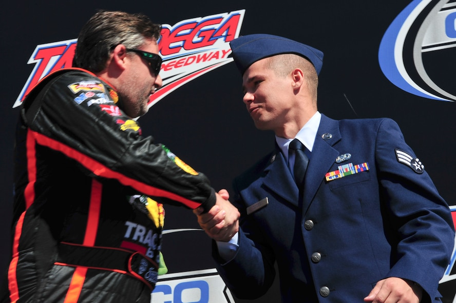 Senior Airman Donald Googe Jr., 42nd Air Base Wing Legal Office paralegal, shakes hands with NASCAR driver Tony Stewart during the Geico 500 Talladega Superspeedway pre-ceremony in Talladega, Ala., Oct. 19, 2014. The ceremony included remarks from special guests and showcased the 43 drivers participating in the race. (U.S. Air Force photo by Airman 1st Class Alexa Culbert)