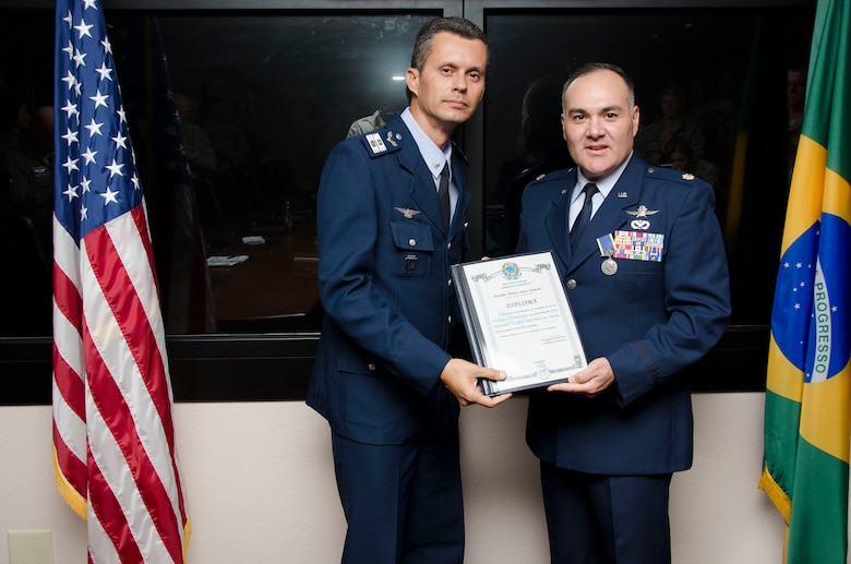Col Alexandre Alves, Brazilian Air Force Liaison Officer to 12th Air Force (Air Forces Southern) presents Maj. Oscar Parra, 12th Air Force (Air Forces Southern) Regional Affairs Strategist, with the Brazilian Air Force Santos-Dumont Medal before a staff meeting on Oct. 22, 2014 at Davis-Monthan AFB, Ariz. The medal is granted by the commander of the Brazilian Air Force, General Juniti Saito, to individuals who have made valuable contributions to the Brazilian Air Force. Parra's dedication has directly influenced the success of several bilateral engagements, utilizing his personal and professional knowledge of international relations to move the mission forward; to include working with his leadership in order to advocate for emerging events, not initially available for the Brazilian Air Force. (U.S. Air Force photo by Staff Sgt. Adam Grant/Released)
