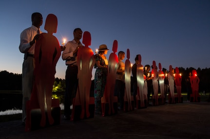 Volunteers hold cardboard references to victims during the Candlelight Vigil at the Municipal Building in Goose Creek, S.C., Oct. 21, 2014. The cutouts were symbols of the victims who have perished due to domestic violence within the last year. The Candlelight Vigil was held in remembrance of the victims of domestic violence in South Carolina. (U.S. Air Force photo/Senior Airman George Goslin)