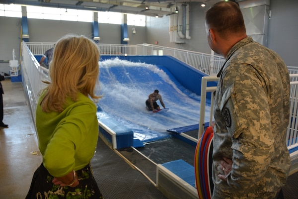 Army Staff Sgt. Angel Perez shows off his boogie boarding skills for Dr. Jill Biden and Col. Don Gajewski, director of the Center for the Intrepid, during Biden's visit to Brooke Army Medical Center, Oct. 22, 2014. The CFI is BAMC's outpatient rehabilitation center. U.S. Army photo by Robert Shields