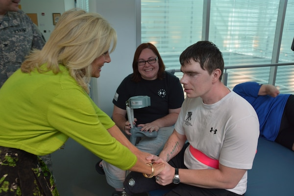 Dr. Jill Biden greets Army Sgt. Cory Muzzy and his wife, Michelle, at the Center for the Intrepid, Brooke Army Medical Center's outpatient rehabilitation center, Oct. 22, 2014. Muzzy was injured in an artillery training accident at Fort Bragg, N.C., in February, losing most of his vision, his right leg above the knee and his left leg below the knee. U.S. Army photo by Robert Shields