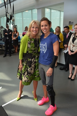 Dr. Jill Biden visits with Army 1st Lt. Kelly Elmlinger, from Brooke Army Medical Center's Warrior Transition Battalion, at the Center for the Intrepid, Oct. 22, 2014. Elmlinger dominated at the Invictus Games for warrior-athletes in London, competing in track, field, cycling, swimming, wheelchair racing and cycling. U.S. Army photo by Robert Shields