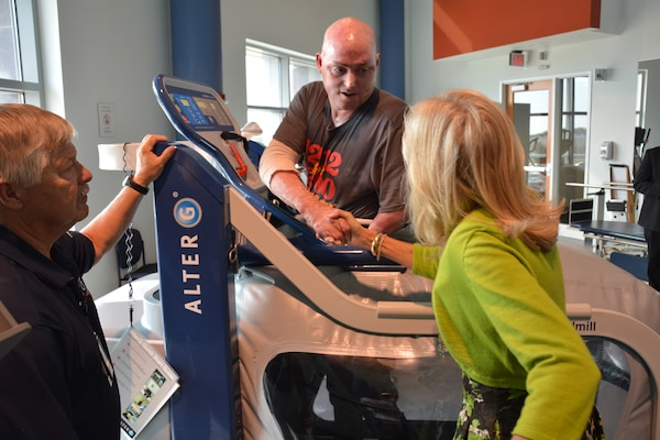 Dr. Jill Biden thanks Marine Corps Lt. Col. Bryan Forney for his service after his workout on an AlterG treadmill while physical therapist Mark Heniser stands by during her visit to the Center for the Intrepid, Oct. 22, 2014. Forney, a Marine Corps CH-46 pilot, was injured while participating in operations in Thailand in 2013. U.S. Army photo by Robert Shields