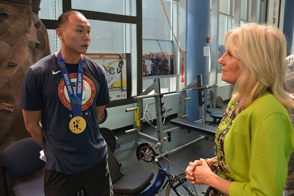 Dr. Jill Biden admires Army Staff Sgt. Jen Lee's gold medal during their talk at the Center for the Intrepid, Oct. 22, 2014. Lee, who lost his left leg above the knee in a motorcycle accident, is a member of the U.S. National Sled Hockey Team that took gold at the Paralympic Winter Games in Sochi, Russia, in March. U.S. Army photo by Robert Shields
