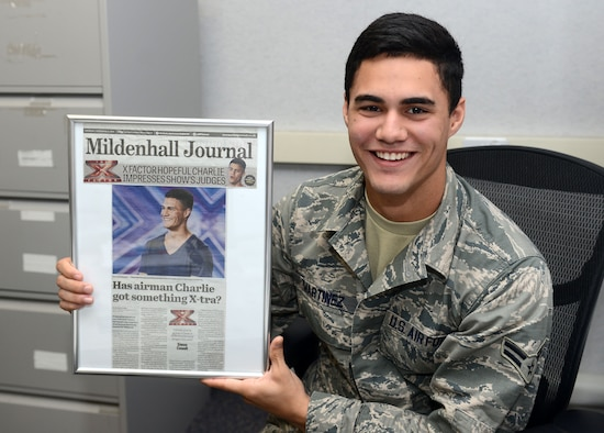 Airman 1st Class Charlie Martinez, 100th Force Support Squadron force management apprentice from Orlando, Fla., poses for a photograph with a newspaper clipping of himself Oct. 15, 2014, on RAF Mildenhall, England. The clipping was from Martinez's time on X Factor United Kingdom, a televised British singing competition. (U.S. Air Force photo/Senior Airman Kate Maurer)
