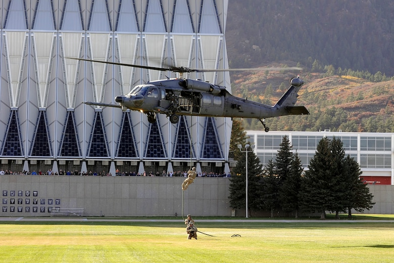 Pararescuemen fast-rope from a hovering HH-60G Pave Hawk Oct. 17, 2014, as it hovers over the cadet area at the Air Force Academy in Colorado Springs, Colo. The pararescuemen, from the 58th Rescue Squadron at Nellis Air Force Base, Nev., and combat rescue officers, from the 23rd Wing at Moody Air Force Base, Ga., performed a combat search and rescue demonstration at the Academy to expose the Cadet Wing to the Air Force combat rescue mission. (U.S. Air Force photo/Bill Evans)