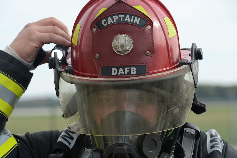 Tech. Sgt. Ryan Atoigue adjusts a light attached to his helmet while participating in structural fire training Oct. 20, 2014, at Dover Air Force Base, Del. Atoigue's helmet indicates that he is a firecrew captain with the 436th Civil Engineer Squadron. (U.S. Air Force photo/Greg L. Davis)