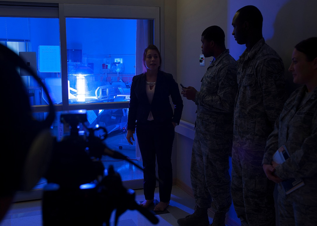 """Geri Genant, left, demonstrates the capabilities of """"Saul"""", a germ-zapping robot, to Airmen Oct. 20, 2014, at Joint Base Langley-Eustis, Va. The 633rd Medical Group partnered with Xenex Healthcare Services, Saul's creator of the robot in effort to provide a safer healthcare facility for the Langley community. Genant is the Xenex Healthcare Services implementation manager. (U.S. Air Force photo/Staff Sgt. Antoinette Gibson)"""