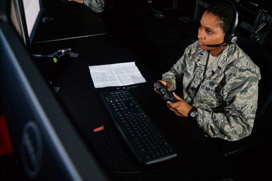 First Lt. Kristin Spencer watches a video for suspicious behavior during a demonstration of a new Enhanced Reporting, Narrative Event Streaming Tool developed by the Air Force Research Laboratory Oct. 15, 2014, at Wright-Patterson Air Force Base, Ohio. The program aims to make intelligence analyst's jobs easier by streamlining some of their routine tasks, which could enable to them save more lives. Spencer is a 711th Human Performance Wing behavioral scientist. (U.S. Air Force photo/Wesley Farnsworth)
