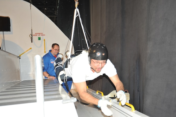 U.S. Space & Rocket Center crew trainer Chris Gorman supervises as Alfonso Santa, an architect with the Operations and Maintenance Medical Engineering Enhancement division under the U.S. Army Engineering and Support Center, Huntsville's Engineering Directorate, simulates weightlessness as he travels along the bay of a space shuttle mock-up and the U.S. Space & Rocket Center during the Center's Leadership Development Program II exercise during a Space Camp corporate camp wich provides training and development programs tailored to achieve the objectives LDP II.