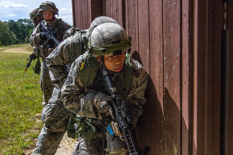 Airmen from the 108th Security Forces Squadron prepare to enter a building during an assault on opposing forces at an urban terrain facility at Joint Base McGuire-Dix-Lakehurst, N.J., Sept. 14, 2014. The Security Forces Airmen practiced land navigation, weapons proficiency and squad maneuvering tactics during September's unit training assembly. (U.S. Air National Guard photo by Master Sgt. Mark C. Olsen/Released)