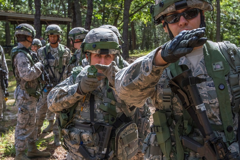Senior Airman Dennis P. Novello, holding compass, provides maneuvering directions to Senior Airman Craig M. Thompson, as the 108th Security Forces Squadron team enters the woods for scenario based training at Joint Base McGuire-Dix-Lakehurst, N.J., Sept. 14, 2014. The Security Forces Airmen practiced land navigation, weapons proficiency and squad maneuvering tactics during September's unit training assembly. (U.S. Air National Guard photo by Master Sgt. Mark C. Olsen/Released)