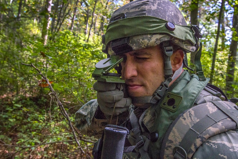 Senior Airman Dennis P. Novello, shoots an azimuth as the 108th Security Forces Squadron team moves through the woods to the military operations in urban terrain facility at Joint Base McGuire-Dix-Lakehurst, N.J., Sept. 14, 2014. Security Forces Airmen practiced land navigation, weapons proficiency and squad maneuvering tactics during September's unit training assembly. (U.S. Air National Guard photo by Master Sgt. Mark C. Olsen/Released)