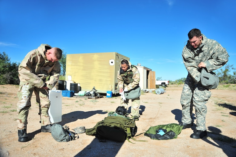 Team members rush to put on mission oriented protective posture gear during an exercise at Davis-Monthan Air Force Base, Ariz., Oct. 23, 2014.  During this station, the teams were given the option to complete a MOPP worksheet or don MOPP level four gear without making any mistakes.  (U.S. Air Force Photo by Airman 1st Class Chris Massey/Released)