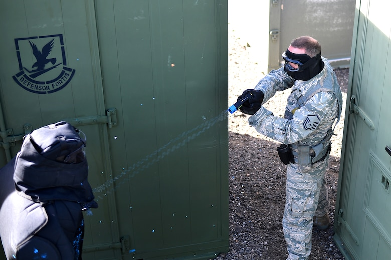 Master Sgt. Don Werkmeister, 140th Security Forces Squadron operations flight sergeant, simulates using a Conducted Electronic Weapon on a suspect during training Oct. 23, 2014, at the 140th SFS building on Buckley Air Force Base, Colo. CEW training is designed to educate law enforcement members on when and how to use non-lethal force in stressful situations. (U.S. Air Force photo by Senior Airman Darren Scott/Released)