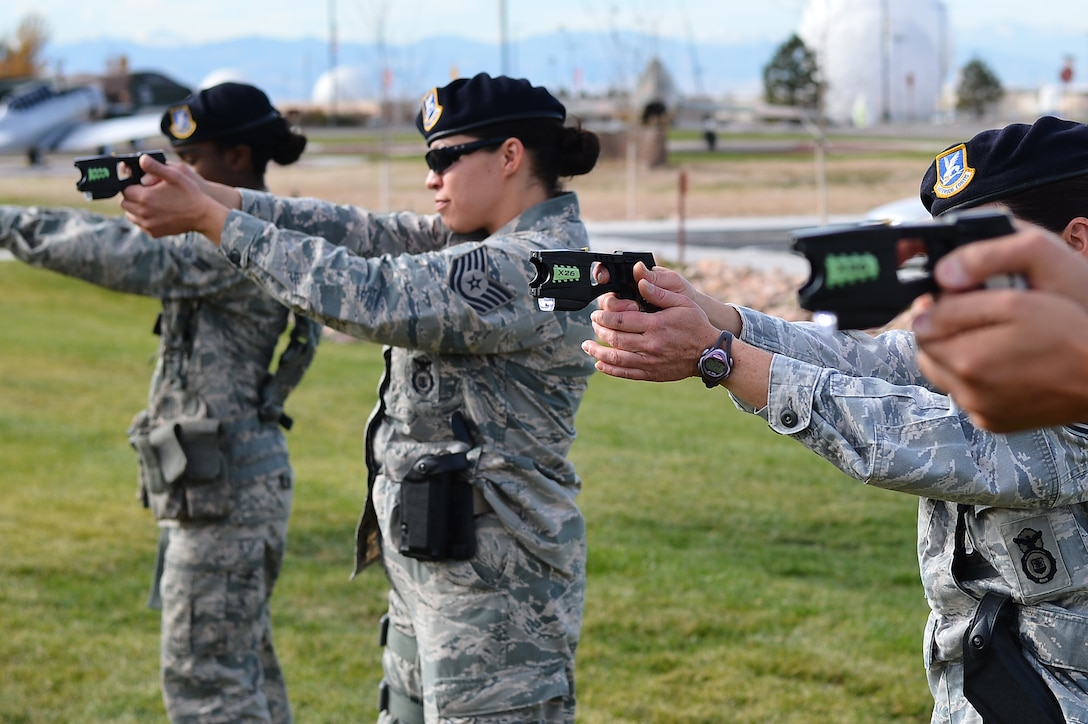 Members from the 140th Security Forces Squadron practice drawing their Conducted Electronic Weapons during training Oct. 23, 2014, at the 140th SFS building on Buckley Air Force Base, Colo. CEW training is designed to educate law enforcement members on when and how to use non-lethal force in stressful situations. (U.S. Air Force photo by Senior Airman Darren Scott/Released)