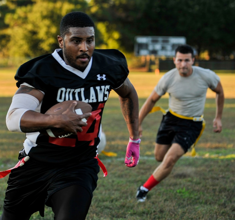 Senior Airman Ryan Galbrieth, 628th Civil Engineer Squadron structural technician, runs the ball past 437th Aircraft Maintenance Squadron defenders  Airman 1st Class Mohamed Alzer (left) and Senior Airman Kevin Medina, during an intramural flag football game Oct. 21, 2014, at Joint Base Charleston, S.C. The 628th CES won 24-14. (U.S. Air Force photo/Staff Sgt. Renae Pittman)